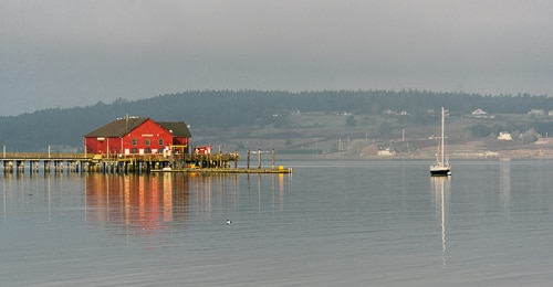 An old style wharf with a red building in it. A sailboat is nearby.