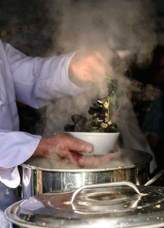 A left hand ladling mussels into a bowl held by the right hand. There is steam all around.