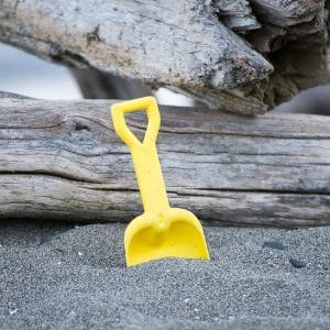 A yellow toy shovel stuck in the sand on one of Whidbey Island's many public beaches.
