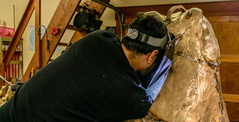 Victor Ramos welding, his head practically inside the back of a giant bronze frog.