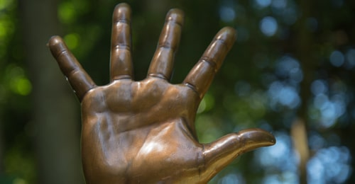 An open hand made of bronze is upraised.
