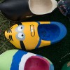 "A miniature wooden shoe decorated like a cartoon ""minion."""